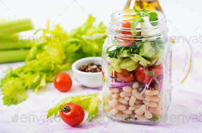 Salad of white beans, tomato, celery, cucumber, arugula, red onion and feta cheese in a jar.