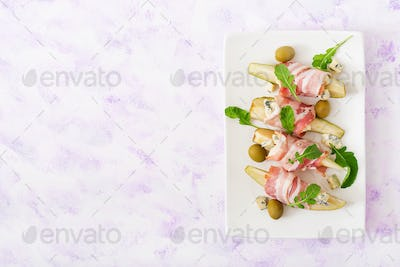 Appetizer with pear, blue cheese, prosciutto ham and toast for holidays