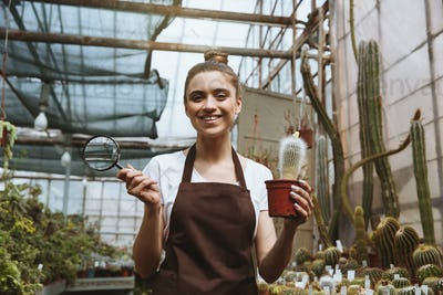 Smiling young woman standing in greenhouse near plants
