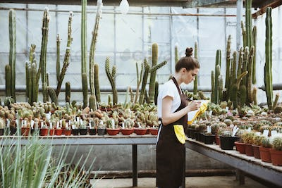 Serious young lady standing in greenhouse holding clipboard