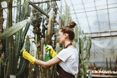 Concentrated young lady in glasses standing in greenhouse