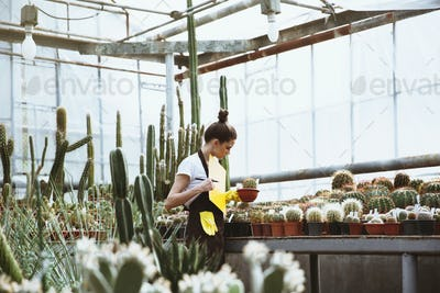 Concentrated young lady standing in greenhouse