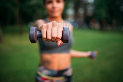 Sporty girl exercise with dumbbells in park