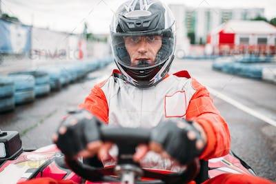 Carting race, go kart driver in helmet, front view