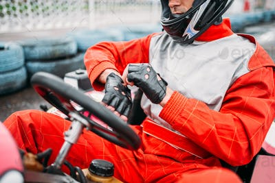 Go-kart driver in helmet on karting speed track