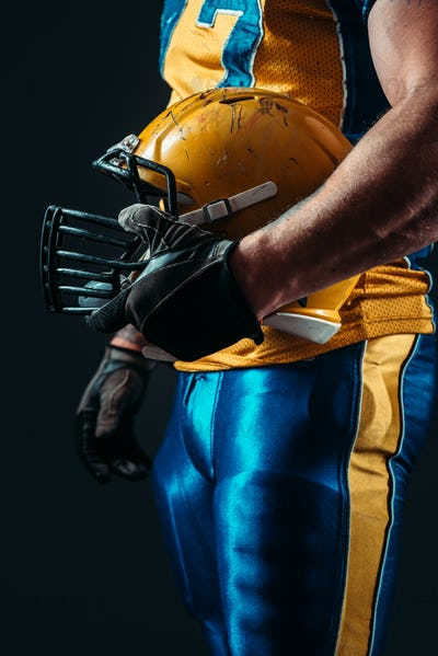 Player with american football helmet in hand