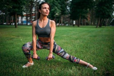 Slim woman exercise with dumbbell in summer park