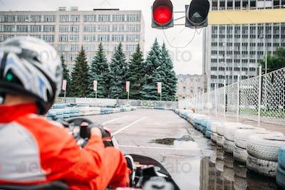 Go kart driver on start line, back view