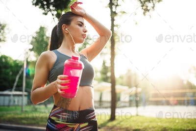 Woman with sport bottle, training in summer park