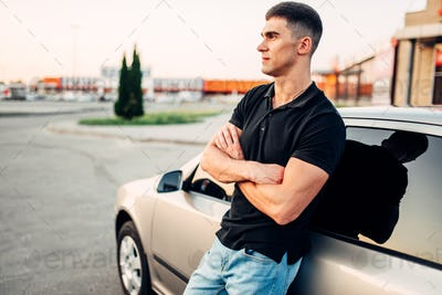 Smiling man standing near his car outdoors