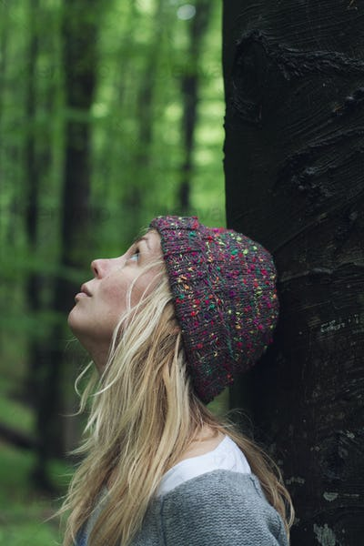 young woman in the green woods looking up