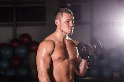 man working out in gym doing exercises with dumbbells at biceps
