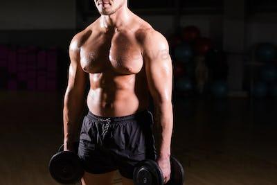 Muscular bodybuilder guy doing exercises with dumbbells.