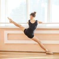 Ballet student practicing at barre in ballet class