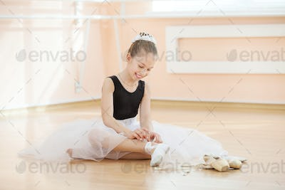 Young balerina changing dancing shoes to pointe ones while sitting on floor