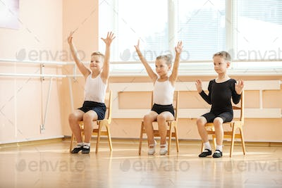 Young dancers playing or doing exercise while sitting on chairs at ballet class
