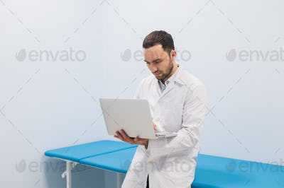 Portrait of cheerful doctor sitting at the desk working on laptop