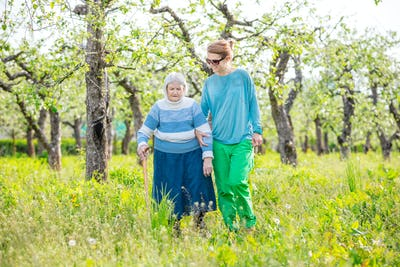 Senior woman supported by granddaughter walking