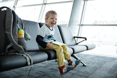 Little boy laughing while watching something on his tablet in an airport departure hall