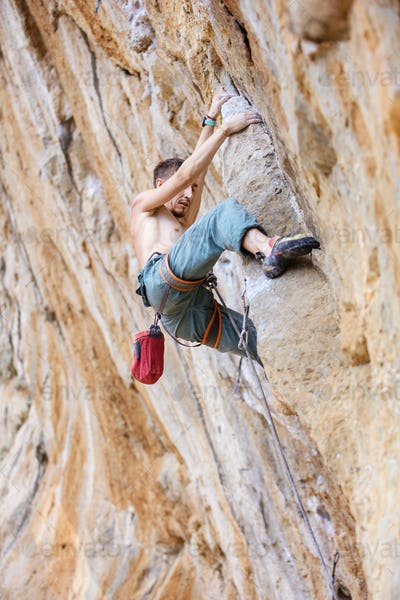 Male rock climber on a face of a cliff