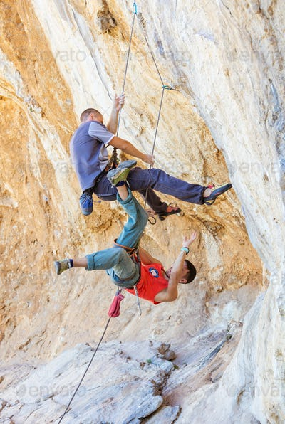 Two male climbers hanging on a rope.