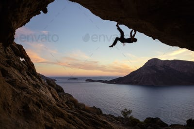 Male climber climbing along roof in cave against beautiful view of coast below