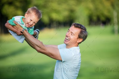 Father and toddler son having fun in summer park