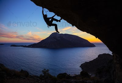 Young man climbing along roof in cave at sunset