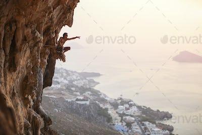 Young man climbing vertical cliff at sunset