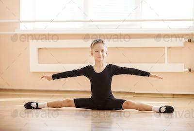 Boy dancer doing splits while warming up at ballet dance class