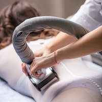 Young woman in spa salon, beautician performing vacuum roller massage