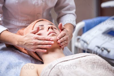 Young woman in spa salon, beautician performing facial massage