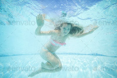 Beautiful young woman swimming underwater in pool