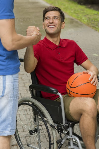 Happy disabled man holding a basketball