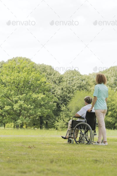 Young nurse with senior woman in middle of the garden