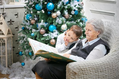Senior woman reading a book to her grandson beside a Christmas tree