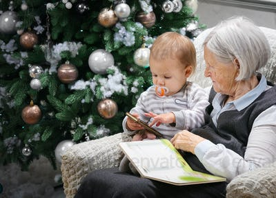Senior woman reading a book to her baby grandson beside a Christmas tree