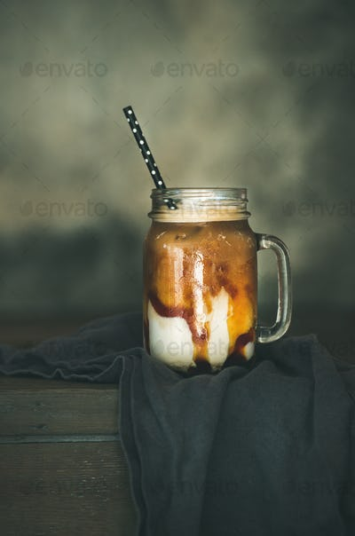 Iced caramel macciato coffee with milk in jar, copy space