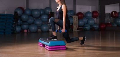 Fitness woman with step platform doing workout