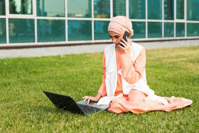 Young Muslim Woman Using Mobile Phone and Laptop In Park