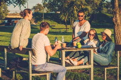 Multi-ethnic group of friends drinking coffee and chatting in a park