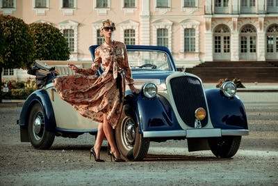 Beautiful lady with bag near classic convertible