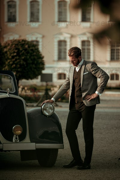 Confident wealthy young man near classic convertible