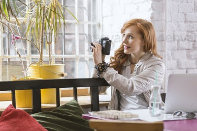 Female photographer in trendy cafe