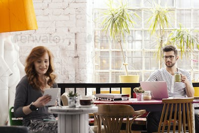 Two hipsters working in modern cafe