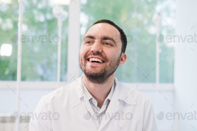Portrait Of Happy Doctor at hospital ward against window