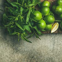 Fresh limes and mint on board for making summer drinks