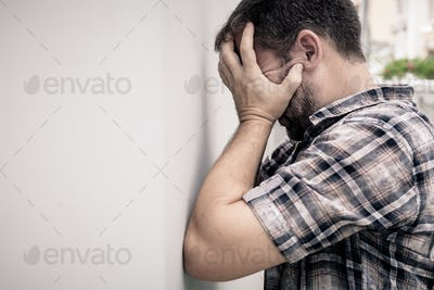 portrait one sad man standing near a wall and covers his face