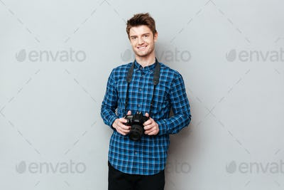 Smiling man holding camera in hands