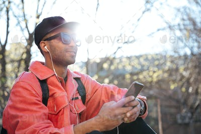 Handsome smiling young african man outdoors using mobile phone.
